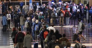 Travelers wait in line to go through the security area at Reagan National Airport on November 21, 2016 in Arlington, Virginia.